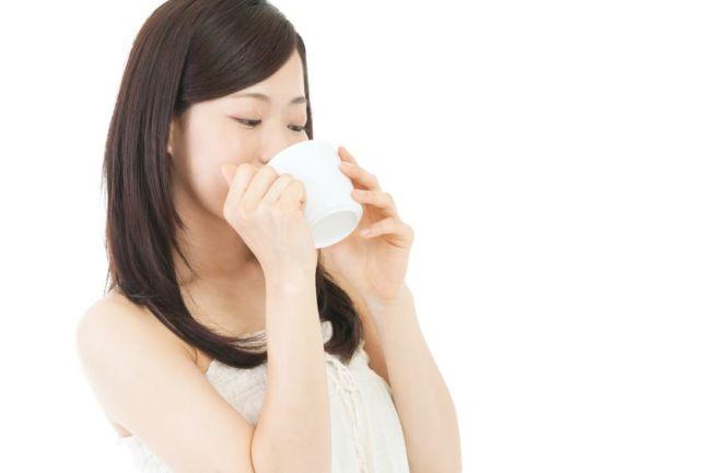 美味しいカフェインレスコーヒーを飲んでいる女性